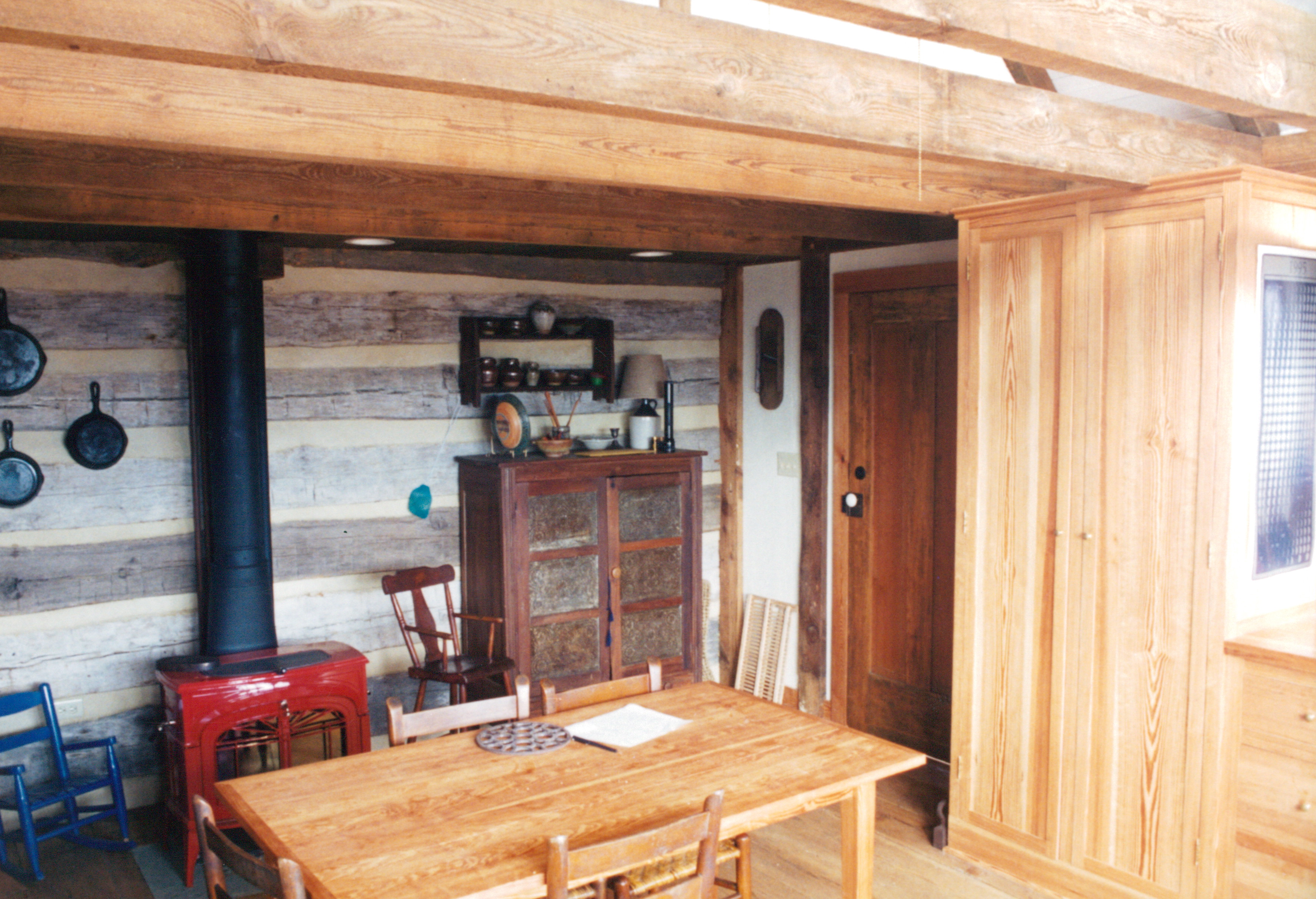 Finished interior where timber frame meets log cabin