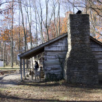 A stone chimney with a log cabin